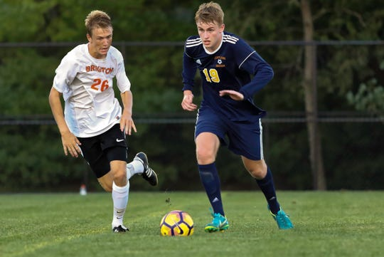Hartland's Brett Kuhlman (19) and Brighton's Joshua Adam race for the ball in the Bulldogs' 1-0 victory over the Eagles on Tuesday Sept. 4, 2018.