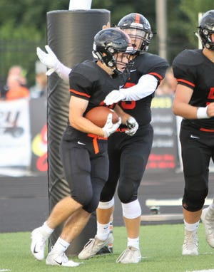 Brighton's Chris Seguin (holding ball) is congratulated after scoring one of his three touchdowns against Novi on Thursday, Aug. 30, 2018.