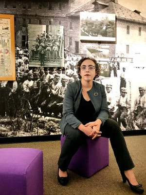 """Suzanne Fischer, museum director at the Michigan History Center, poses by an exhibit on Michigan's boys and girls training schools. A traveling exhibit, """"States of Incarceration,"""" runs Sept. 8 through May 19."""
