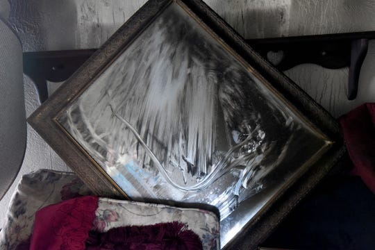 A damaged mirror sits in a pile in the family room at the Blevins home.