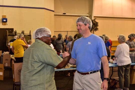 Helping pack shelf-stable food for Mid-South Food Bank are (left to right) Donald R. Ester, Sr., pastor of New Bethel Missionary Baptist Church, and Will Jones, pastor of Germantown Presbyterian Church -- both working at New Bethel Missionary Baptist Church, one of MIFA's CommUNITY Days project sites.