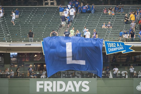 A giant L flag is unfurled by fans at Miller Park after an 11-1 win over the Chicago Cubs.