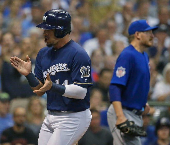 Hernan Perez claps after scoring on a sacrifice fly by Erik Kratz during the fourth inning that gave the Brewers a 2-1 lead over the Cubs.