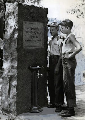 In this 1938 photo, a monument erected in memory of Louis M. Kotecki, a former city comptroller in Milwaukee, is viewed by two boys,  Ralph Czapiewski, left, and Chester Bartosz. The bubblers don't work anymore, but the monument remains in a pocket park on Windlake Avenue and South 15th Street. In 1933, Kotecki committed suicide in his City Hall office after shooting and nearly killing his deputy, William Wendt.
