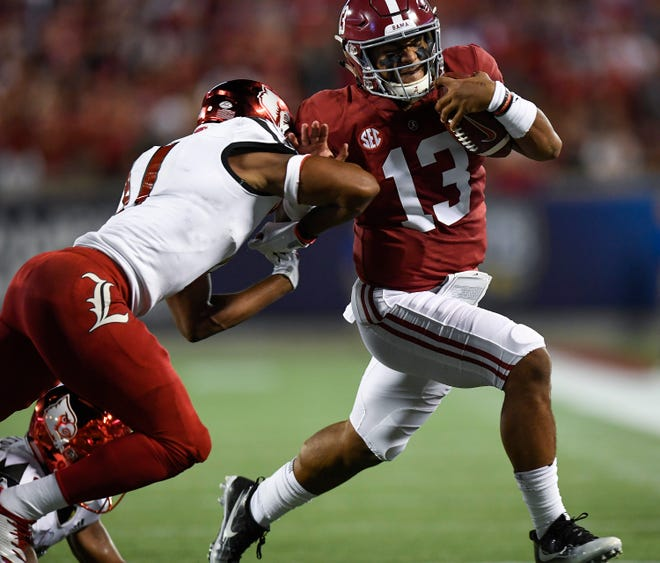 Alabama quarterback Tua Tagovailoa (13) is forced out of bounds by Louisville safety Dee Smith (11) in the first half action of the Camping World Kickoff at Camping World Stadium in Orlando, Fla., on Saturday, September 1, 2018.