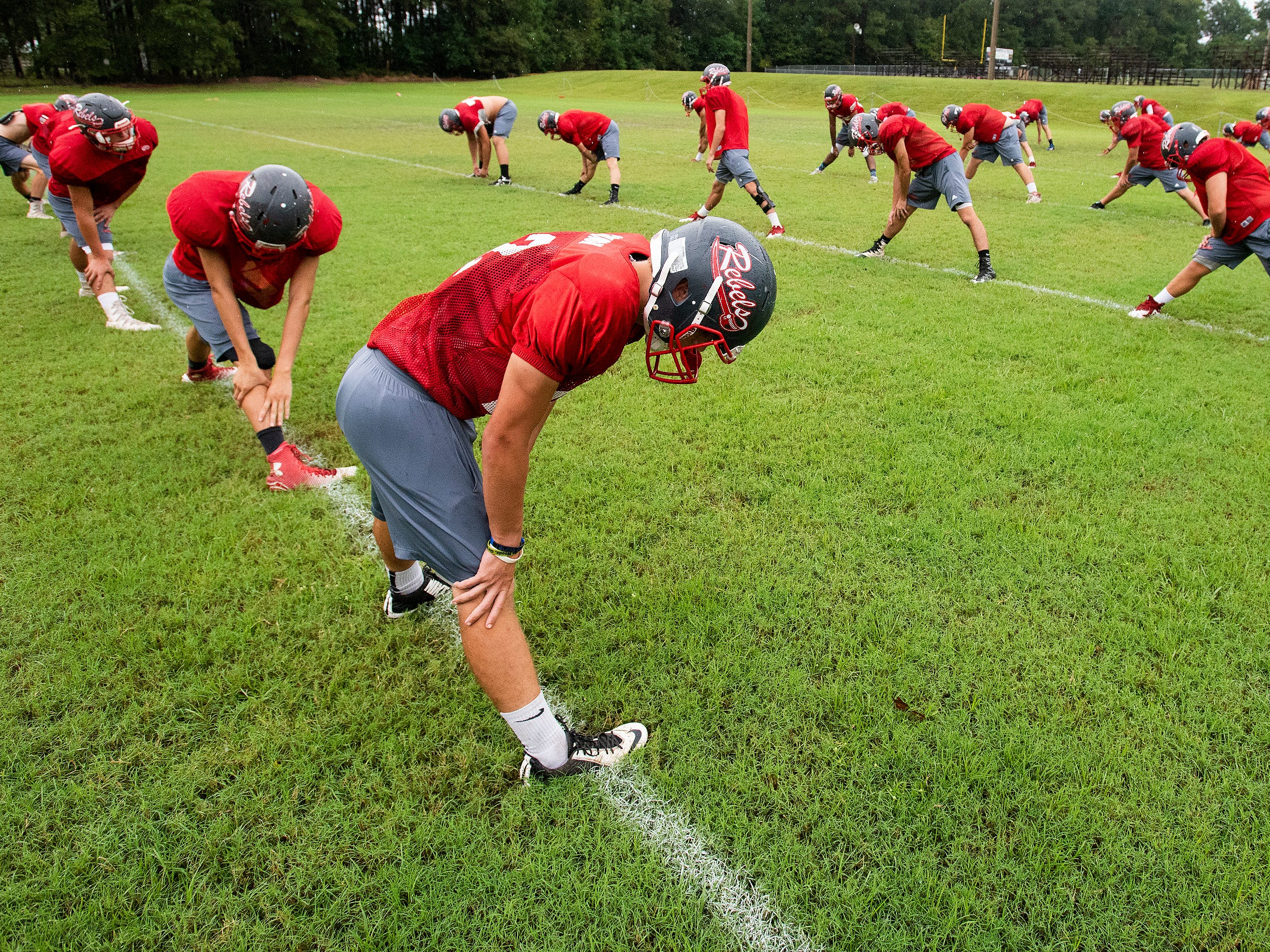 Lowndes Academy players stretch before practice in Hayneville, Ala., on Wednesday September 5, 2018.