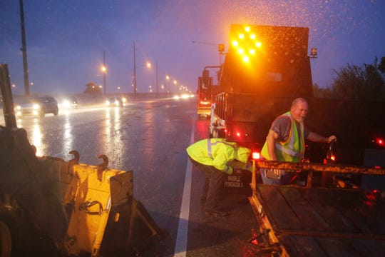 Crew members with the Alabama Department of Transportation work to block off a flooded part of US Highway 98 while fighting rain from Tropical Storm Gordon on Wednesday, Sept. 5, 2018, in Spanish Fort, Ala. (AP Photo/Dan Anderson)