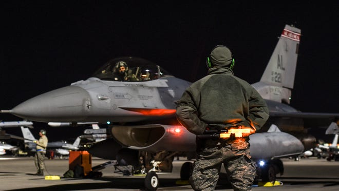 U.S. Air Force Senior Airman James Knight, right, a crew chief with the 187th Aircraft Maintenance Squadron, Montgomery Regional Air National Guard Base, waits after marshaling to U.S. Air Force Capt. Don Roney, a fighter pilot, 100th Fighter Squadron, February 28, 2017, at Nellis Air Force Base, Nev.