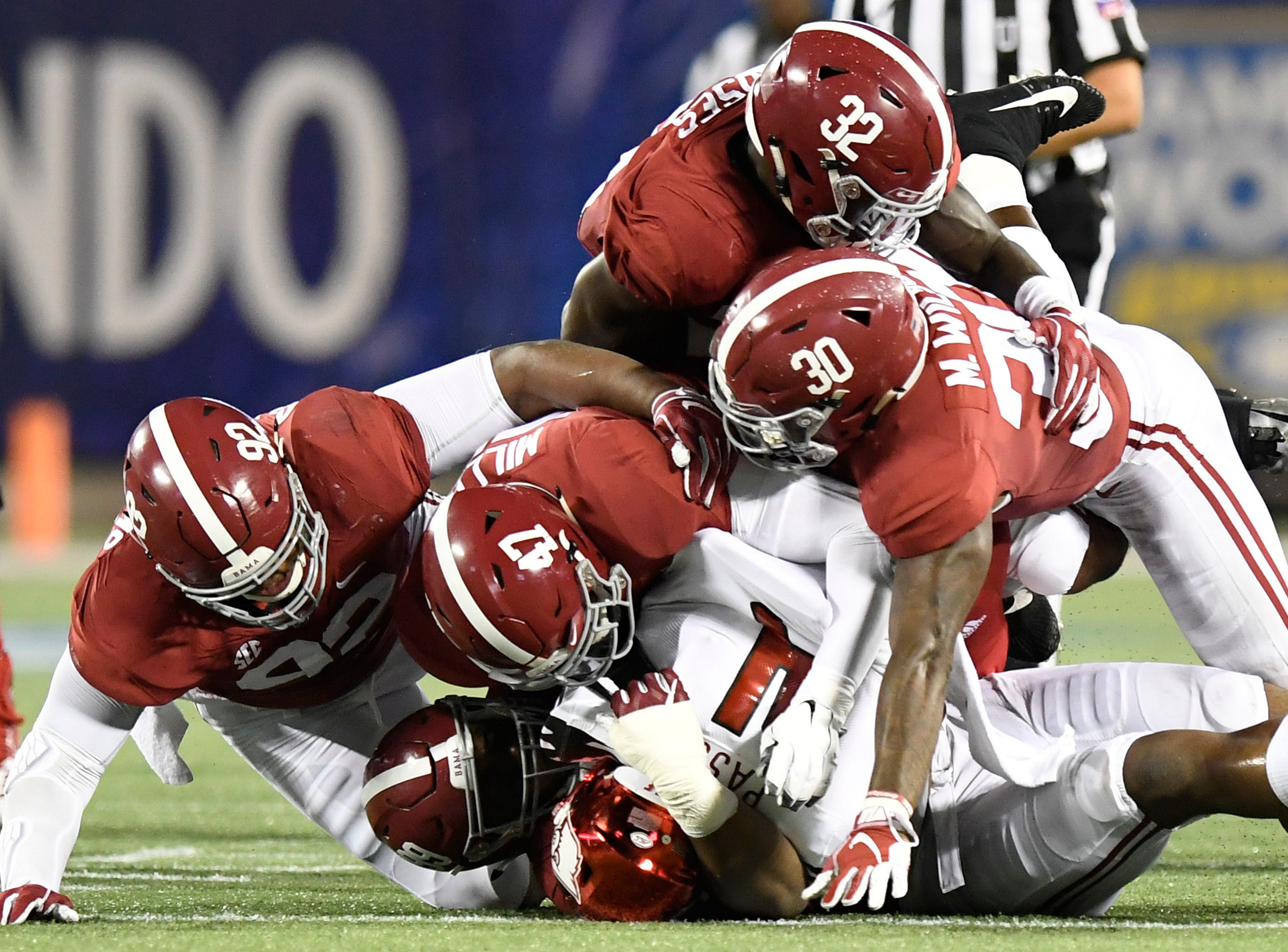 Louisville quarterback Jawon Pass (4) is swarmed by Alabama defenders Raekwon Davis (99), Christian Miller (47), Mack Wilson (30), Dylan Moses (32) and Quinnen Williams (92) in first half action of the Camping World Kickoff at Camping World Stadium in Orlando, Fla., on Saturday September 1, 2018.