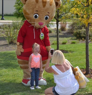 Daniel Tiger poses for a photo with a new friend during Be My Neighbor Day 2017.