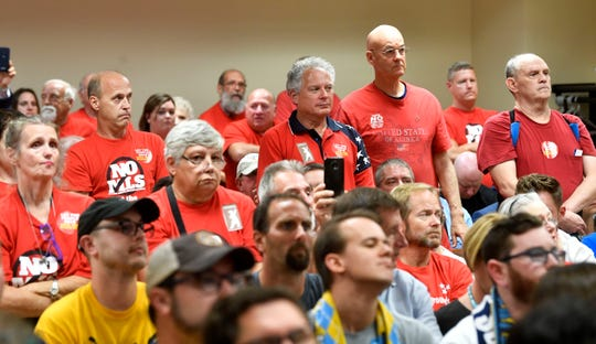 Opponents of the MLS stadium at the fairgrounds stand in support of a council member speaking in their favor on Tuesday.