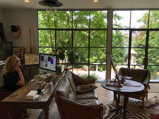 Interior designer and the current owner of the home, Jeannette Whitson, has kept a home office in the restored home. This photo shows the dramatic wall of custom windows with doors leading to the back patio and garden.