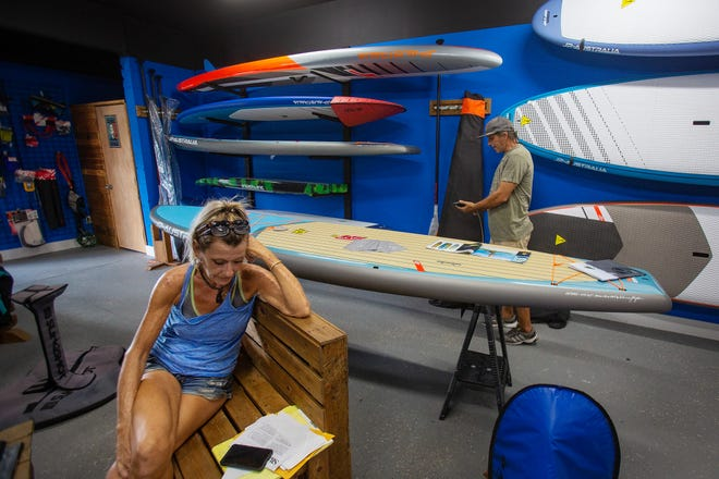 Kelly Gianello, owner of Windstalker's Naples kiteboarding and paddle boarding, looks down at a Small Business Administration loan application she just tore in frustration as her husband, Enrique, works in their shop in Naples on Wednesday, Sept. 5, 2018. The Gianellos did get a $2,000 grant from the Community Foundation of Collier County, which has received 46 applications for hardship assistance to businesses hurting from red tide.