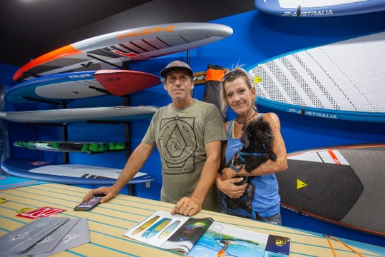 The owners of Windstalker's Naples  kiteboarding and paddle boarding, Enrique and Kelly Gianello, with their dog, Jinx at their shop in Naples on Wednesday, Sep. 5, 2018. The business received a $2,000 hardship grant from the Community Foundation of Collier County, after a disastrous summer due to red tide and the algae bloom.