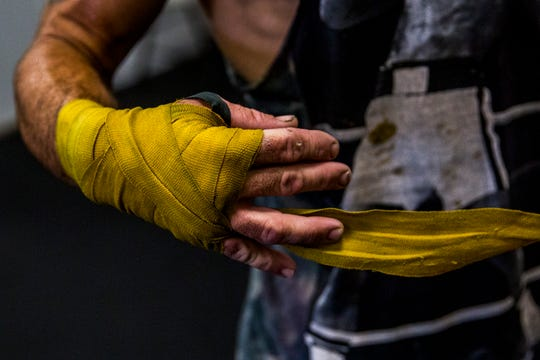 Tommy Bryant Jr., 29, unwraps his hands after finishing training at The Sweet Science boxing gym in East Naples on Tuesday, Sept. 4, 2018.