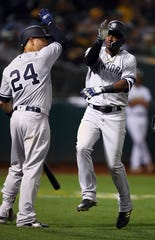 New York Yankees' Adeiny Hechavarria, right, celebrates with Gary Sanchez (24) after hitting a home run off Oakland Athletics' Emilio Pagan during the ninth inning of a baseball game Tuesday, Sept. 4, 2018, in Oakland, Calif.