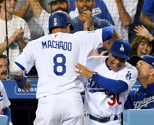 Sep 4, 2018; Los Angeles, CA, USA; Los Angeles Dodgers manager Dave Roberts (30) greets shortstop Manny Machado (8) after he scored from second base on a wild pitch by New York Mets relief pitcher Corey Oswalt (55) in the seventh inning at Dodger Stadium.