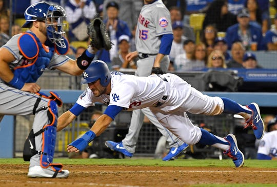 Sep 4, 2018; Los Angeles, CA, USA; Los Angeles Dodgers center fielder Chris Taylor (3) scores on a single by Los Angeles Dodgers catcher Yasmani Grandal (9) as he beats the throw to New York Mets catcher Kevin Plawecki (26) on  in the seventh inning at Dodger Stadium.