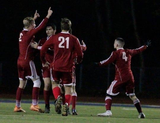 Pompton Lakes' Yianni Ekonomides (9) celebrates with teammates.