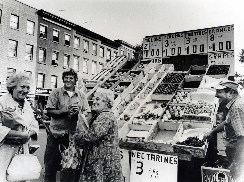 A fruit stand sells fresh produce on the street. (1975)