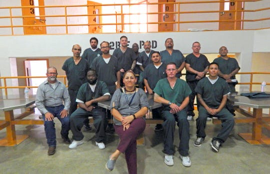 New Mexico State University Cooperative Extension Service agent Jeff Anderson, far left, and prison classification officer Sandra Lopez, center, pose with inmates in GOAL pod, which created a therapeutic garden program at the Southern New Mexico Correctional Facility in 2016.