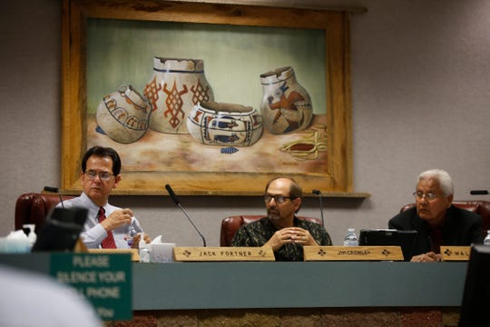 San Juan County Commissioners Jack Fortner, left, Jim Crowley and Wallace Charley vote to pass a resolution regarding straight-party voting Wednesday during a meeting at the county administration building in Aztec.