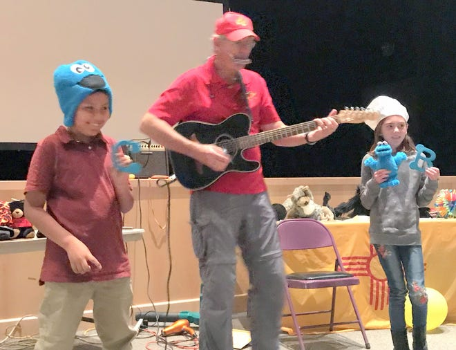"""Lakota Hewgley and Tristan Ortego, both 5th graders, help with the song """"C is for cookie, B is for biscochito!"""""""