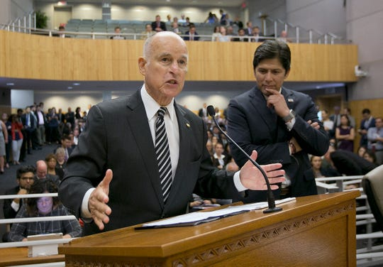 In this July 13, 2017 file photo, Gov. Jerry Brown, left, flanked by Kevin de León, urges members of the California Senate's Environmental Quality Committee to approve a pair of bills to extend the state's cap-and-trade program.