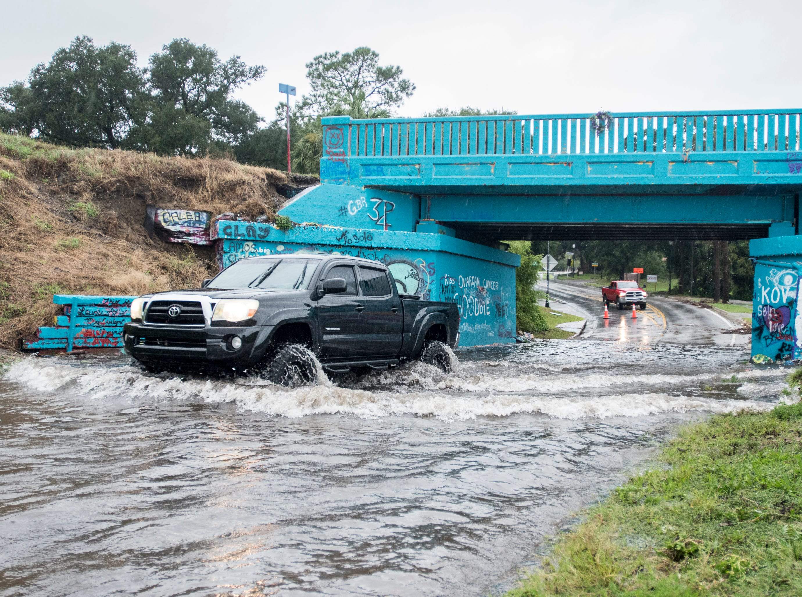 A vehicle with a high suspension makes its way through the flood water under Graffiti Bridge as Tropical Storm Gordon leaves Pensacola on Wednesday, September 5, 2018.