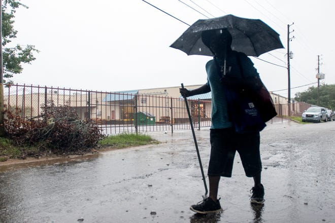 A man makes his way to the Alfred-Washburn Center in Pensacola on Wednesday as rain from Tropical Storm Gordon hammers the area.