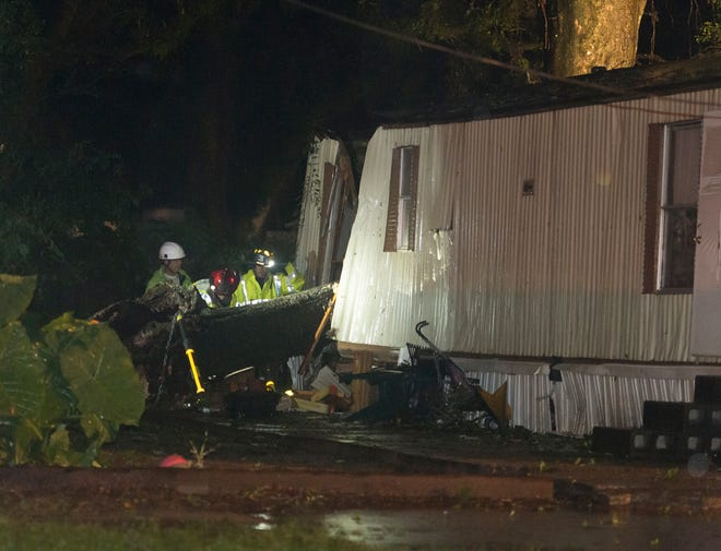 First responders work at the scene of a tree that fell into a mobile home on W. Bobe Street in Pensacola as Tropical Storm Gordon rolls through Pensacola on Tuesday, September 4, 2018.