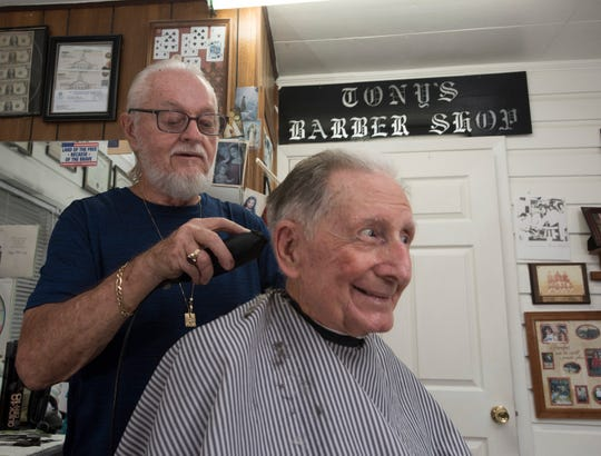 Tony Sordillo, the owner of Tony's Barber Shop on Pine Forest Road, cuts the hair of his former shipmate on the USS Roosevelt, John Johnson, on Wednesday.