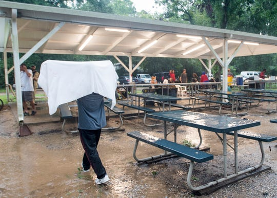 John Roberts, left, uses a towel to shield himself from the rain as he walks to the covered porch at the Alfred-Washburn Center in Pensacola on Wednesday.