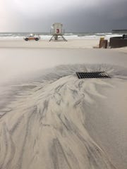 Sand covers the plaza at Casino Beach on Wednesday, Sept. 5, 2018, as rain and winds from Tropical Storm Gordon batter the area.