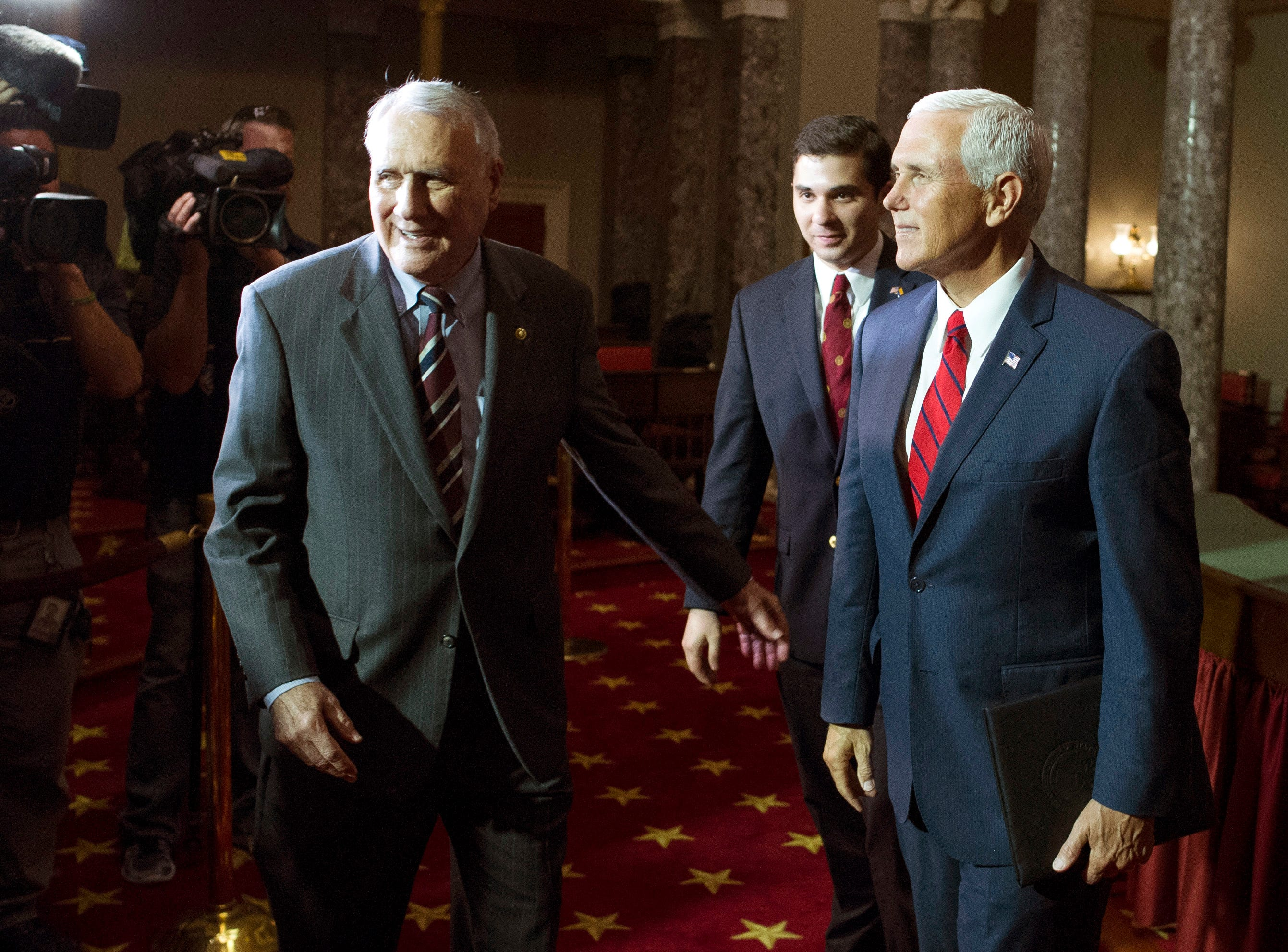 Vice President Mike Pence (right), Sen. Jon Kyl, R-Ariz., (left) and his grandson Christopher Gavin, leave the Old Senate Chamber after a ceremonial swearing-in for Kyl on Capitol Hill, in Washington, on Sept. 5, 2018.