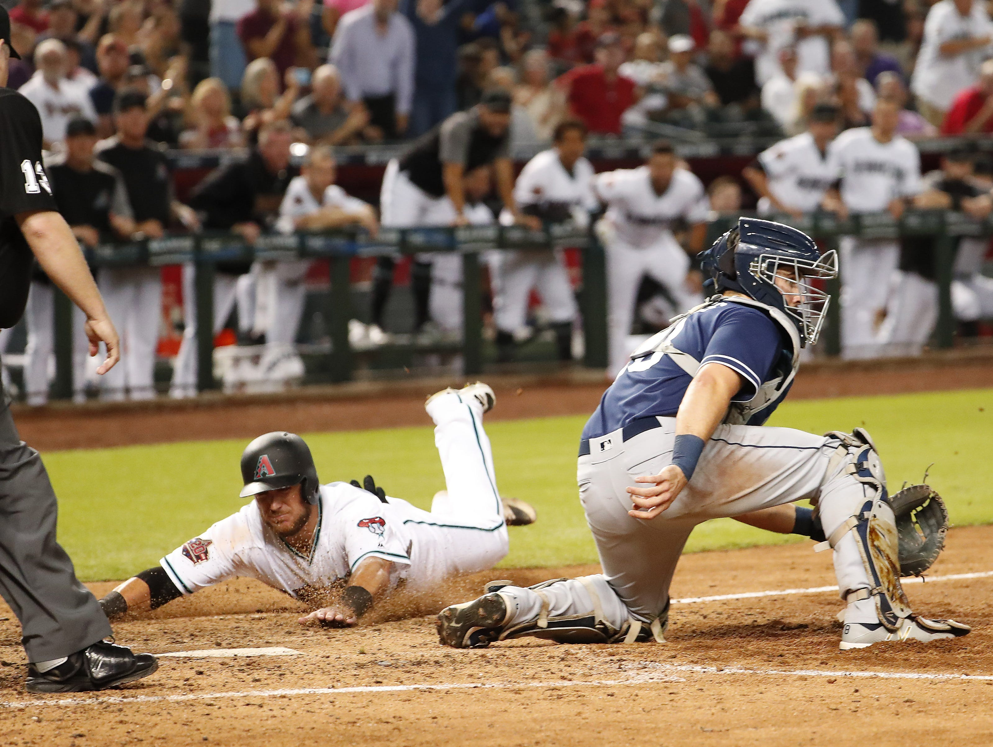 Arizona Diamondbacks catcher Jeff Mathis (2) scores ahead of the tag by San Diego Padres catcher Austin Hedges (18) during the seventh inning at Chase Field in Phoenix, Ariz. Sept. 4, 2018.
