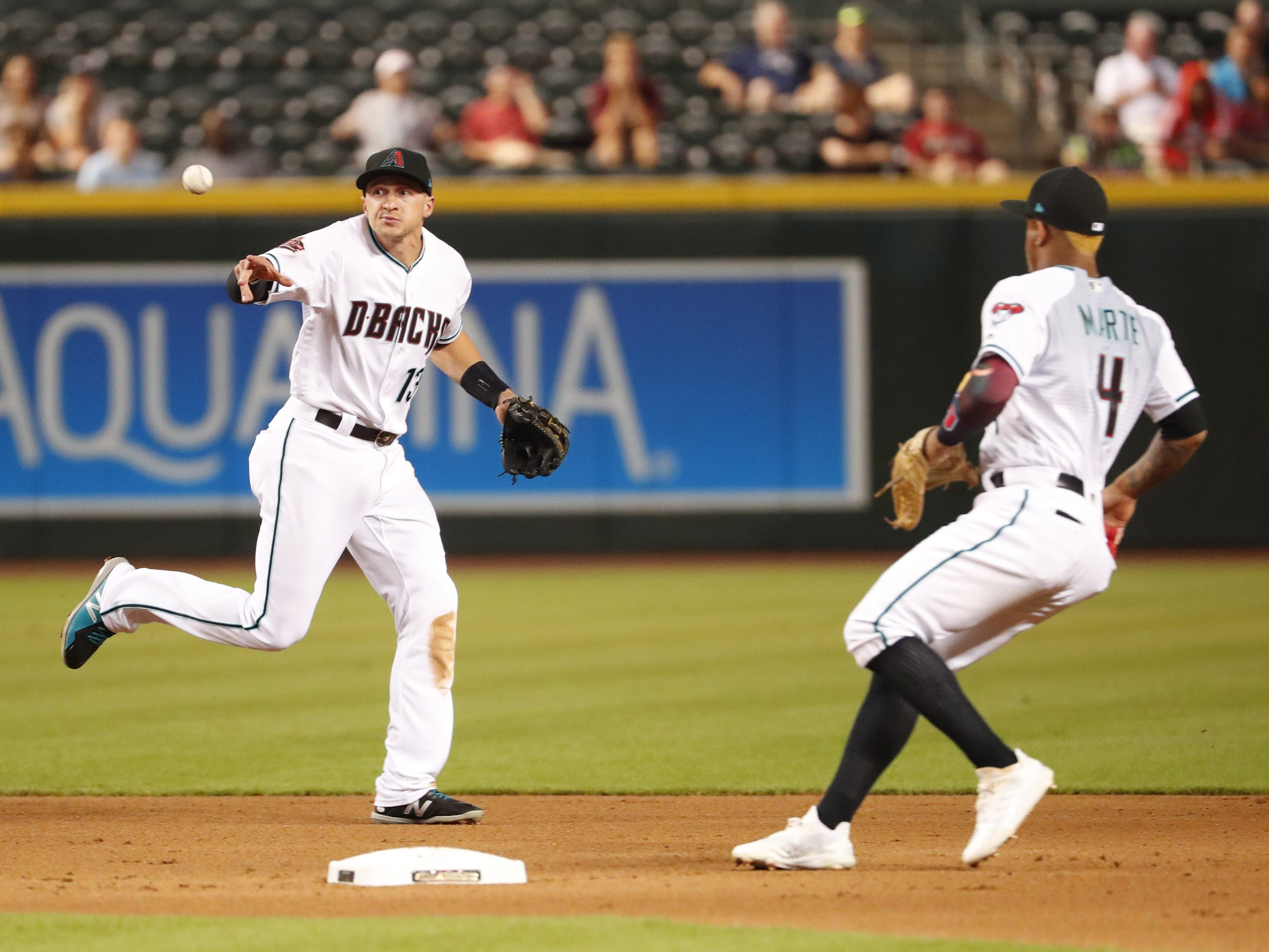 Arizona Diamondbacks shortstop Nick Ahmed (13) flips the ball to second baseman Ketel Marte (4) to start a double play against the San Diego Padres during the fifth inning at Chase Field in Phoenix, Ariz. September 4. 2018.