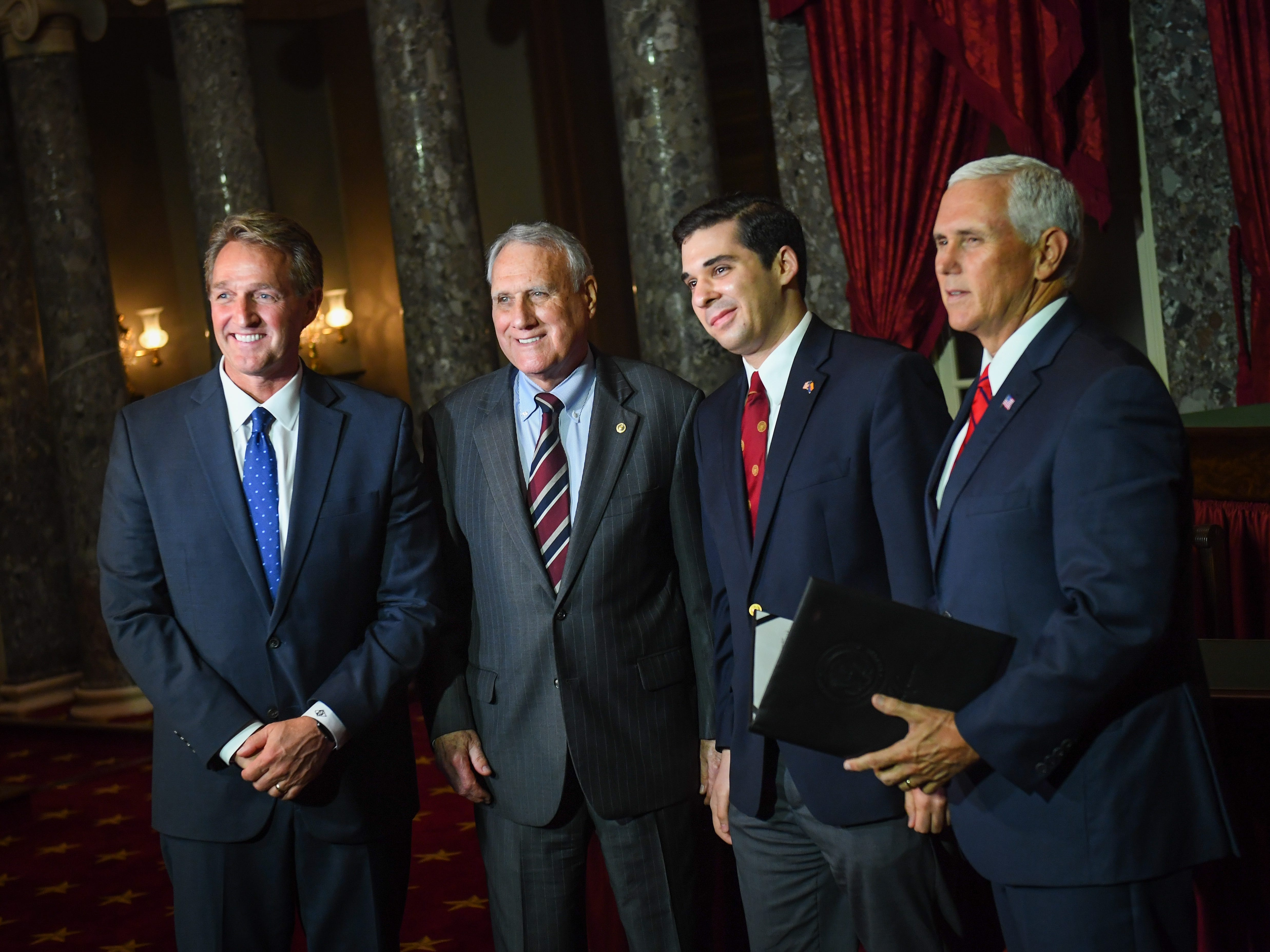 Senator Jeff Flake, R-Ariz., left, offers congratulations to Jon Kyl after he was sworn-in by Vice President Mike Pence during a reenactment ceremony on Sept. 5, 2018 in Washington along with Kyl's grandson Christopher Gavin.