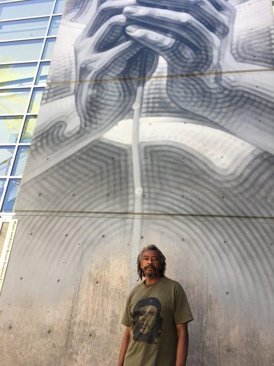 """Phoenix artist Joe Willie Smith outside Mesa Contemporary Arts Museum. Murual: """"Desert Rose Nuevas Generaciones"""" by El Mac."""