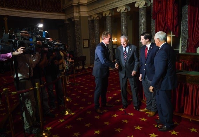 Sen. Jeff Flake, R-Ariz., left, offers congratulations to Jon Kyl after he was sworn-in by Vice President Mike Pence during a reenactment ceremony on Sept. 5, 2018, in Washington along with Kyl's grandson Christopher Gavin.