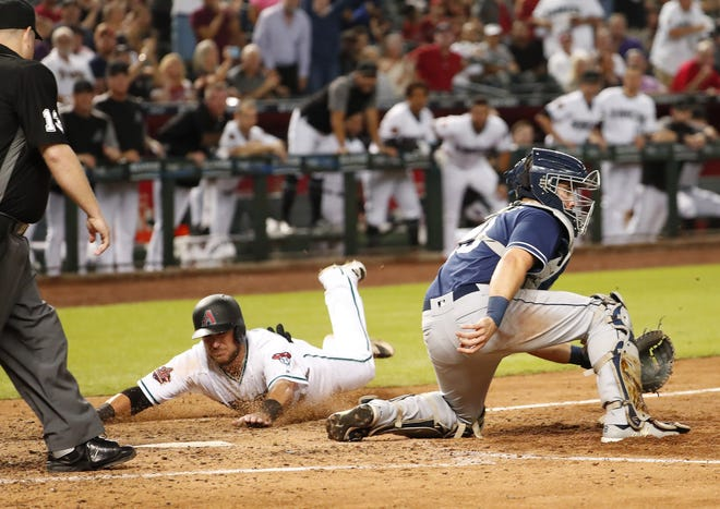 Arizona Diamondbacks catcher Jeff Mathis (2) scores ahead of the tag by San Diego Padres catcher Austin Hedges (18) during the seventh inning at Chase Field in Phoenix, Ariz. September 4. 2018.