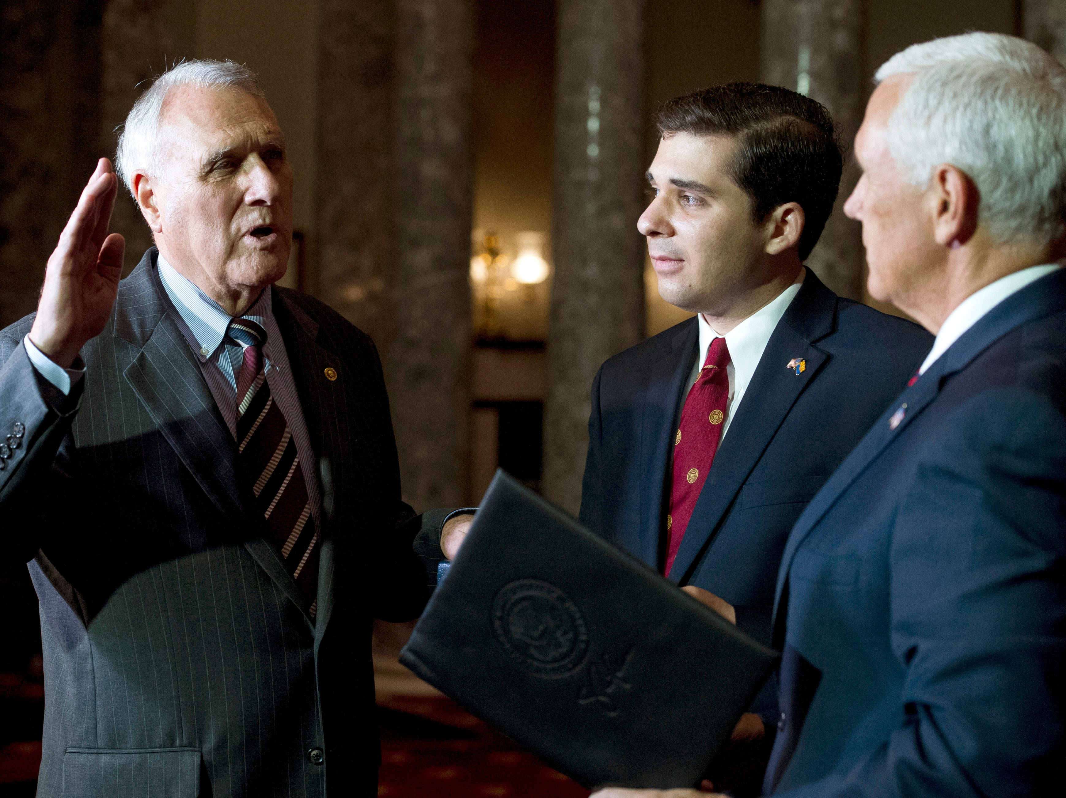 Vice President Mike Pence (right) administers the oath of office to Sen. Jon Kyl, R-Ariz., while his grandson Christopher Gavin holds a Bible, during a ceremonial swearing-in at the Old Senate Chamber on Capitol Hill, in Washington, on Sept. 5, 2018.