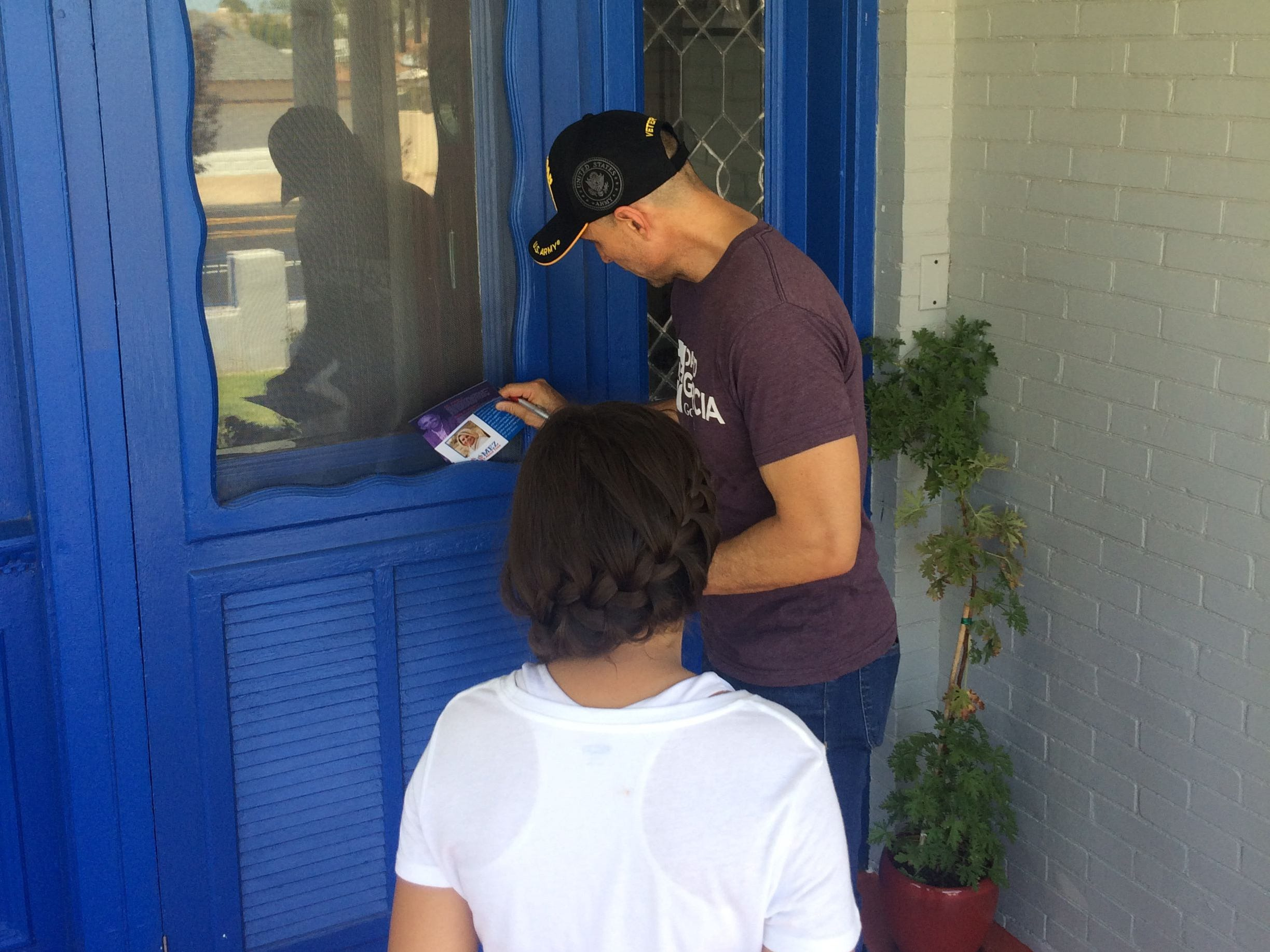 Democratic gubernatorial candidate David Garcia leaves campaign literature at a home in Douglas on Aug. 19, 2018, while his daughter, Lola, looks on.