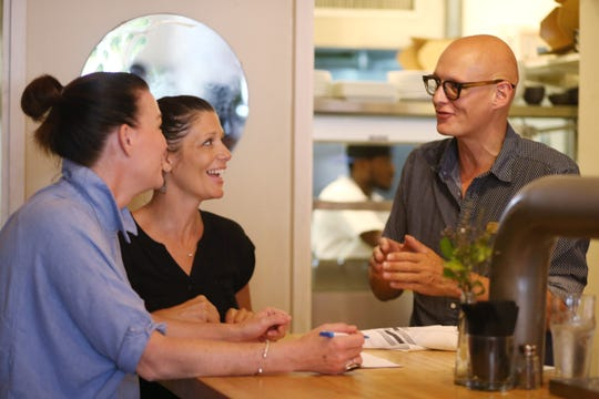 Owner Phillipe Pierre speaks with, from left, general manager Sterling Knight and waitress Vanessa Budetti at Ms. Fairfax on Liberty Street in Newburgh on August 30, 2018.