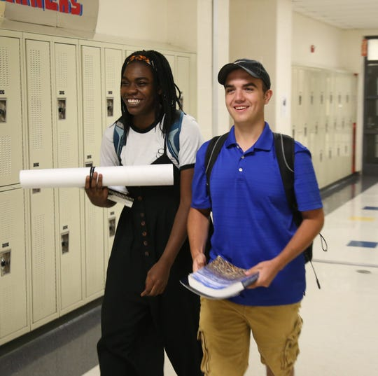 From left, seniors Ennie Akinwunmi and Noah Cory walk to class at Beacon High School on September 5, 2018.
