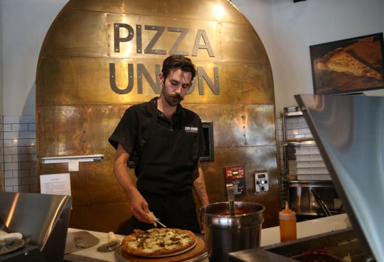 Head pizzaiolo Kevin Mahan puts the finishing touches on a pie at Pizza Union in the Town of Newburgh on August 31, 2018.