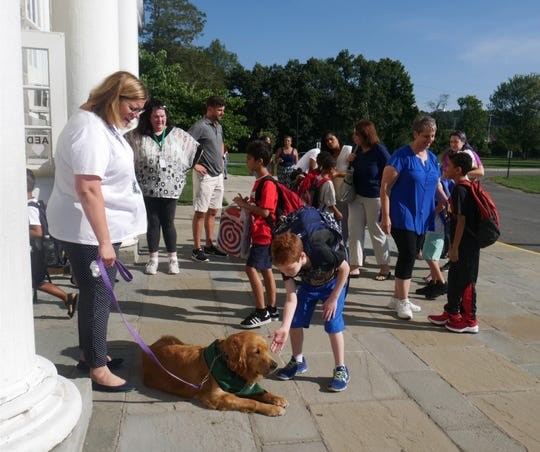 Violet Avenue Elementary School Principal Deanna Gonzalez, accompanied by the school's new service dog, Milano, greets students as classes begin on Sept. 5, 2018.