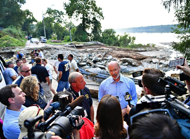 PEMA Director Rick Flinn, center left, looks on as Gov. Tom Wolf addresses media while touring the property of Amy and Paul Nevin that was damaged by flooding on Accomac Road in Hellam Township, Wednesday, Sept. 5, 2018. Dawn J. Sagert photo
