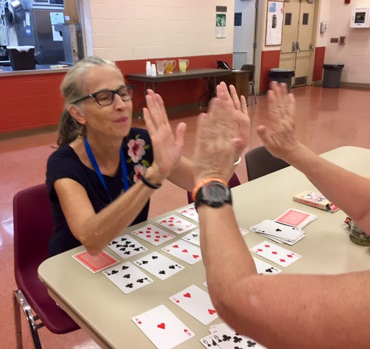 Wendy Anderson, a volunteer at The Coffee Spot resource center for homeless people, plays cards with a client. Open weekdays 1-2:30 p.m. in the Salvation Army building at the corner of King and Duke streets in York, the center offers refreshments, games and mail service for homeless people.