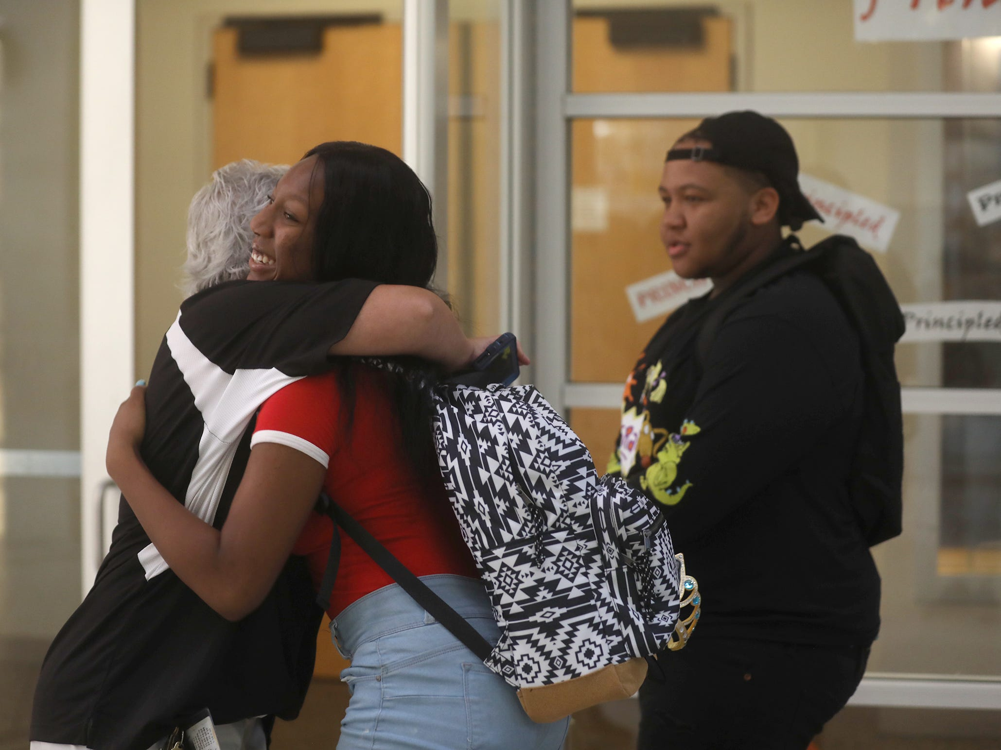 Physical education teacher Chantal Fillion gives a hug to  Rochester Early College International High School students Sha-lami Moore and Ajai Hudson.